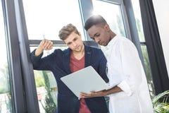 многокультурные уверенно бизнесмены работая на компьтер-книжке совместно Стоковые Фото