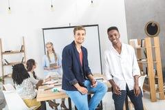 многокультурные усмехаясь бизнесмены смотря камеру и коллеги обсуждая работу позади Стоковые Фотографии RF