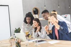 многокультурные excited бизнесмены смотря компьтер-книжку экранируют совместно на рабочем месте Стоковое Фото