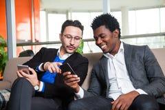 2 многокультурных люд сидят на мобильных телефонах софы, улыбки и владения Стоковая Фотография