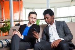 2 многокультурных люд сидят на мобильных телефонах софы, улыбки и владения Стоковое Фото