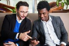 2 многокультурных люд сидят на мобильных телефонах софы, улыбки и владения Стоковое фото RF