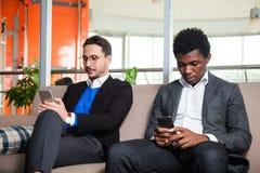 2 многокультурных люд сидят на мобильных телефонах софы, улыбки и владения Стоковое Изображение