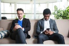 2 многокультурных люд сидят на софе и держат мобильные телефоны Стоковое Фото