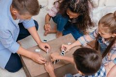 Многокультурная группа в составе дети играя домино на деревянной коробке Стоковая Фотография