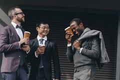 Многокультурные бизнесмены держа бумажные кофейные чашки и положение outdoors Стоковое Изображение