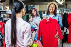 Многокультурные девушки битника выбирая одежды и используя smartphone в бутике Стоковое фото RF