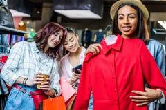 Многокультурные девушки битника выбирая одежды и используя smartphone в бутике Стоковая Фотография