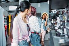 Многокультурные девушки битника выбирая солнечные очки в бутике Стоковые Фотографии RF