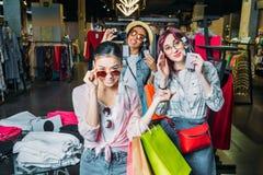 Многокультурные девушки битника выбирая солнечные очки в бутике Стоковое Изображение