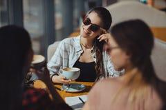 Многокультурные женщины на перерыве на чашку кофе в кафе Стоковые Изображения RF