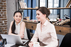 Многокультурные коммерсантки обсуждая проект на рабочем месте с компьтер-книжкой в современном офисе Стоковое Изображение RF