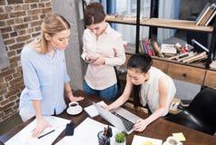 Многокультурные коммерсантки работая с компьтер-книжкой на рабочем месте в современном офисе Стоковое Фото