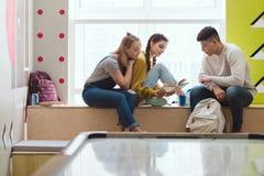Многонациональная группа в составе книга чтения студентов средней школы во время стоковые изображения
