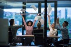 Многонациональная группа в составе молодые бизнесмены бросая документы Стоковое фото RF