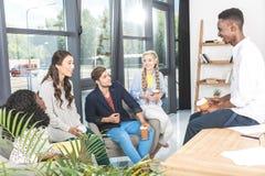 многонациональная группа в составе сотрудники дела имея переговор во время перерыва на чашку кофе Стоковое фото RF