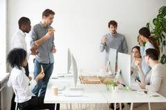 Многонациональная рабочая группа говоря и есть пиццу на рабочем месте Стоковые Фото