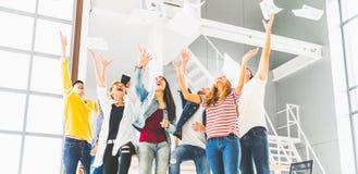 Многонациональная разнообразная счастливая команда празднует бумагу хода успеха проекта вверх совместно Корпоративная община, или стоковое изображение rf