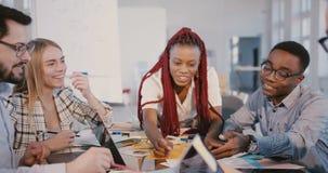 Многонациональная сыгранность на здоровом рабочем месте Опытные молодые черные женские работы руководителя вместе со счастливыми  видеоматериал