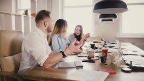Многонациональное обсуждение деловых партнеров на таблице Уверенно боссы компании говорят и обсуждают сроки действия договора 4K акции видеоматериалы