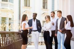 Многонациональные бизнесмены имея перерыв на чашку кофе на балконе офисного здания стоковая фотография rf