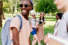 Многонациональные девушки в солнечных очках смотря мальчиков стоя на переднем плане Стоковые Фото