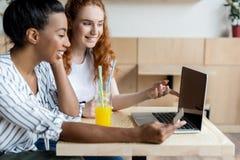 Многонациональные девушки используя компьтер-книжку Стоковое Изображение