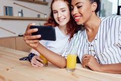 Многонациональные девушки используя smartphone Стоковое Фото