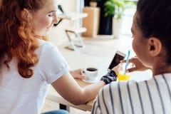 Многонациональные девушки используя smartphone Стоковая Фотография RF