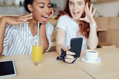 Многонациональные девушки используя smartphone Стоковое Изображение RF