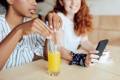 Многонациональные девушки используя smartphone Стоковые Изображения RF