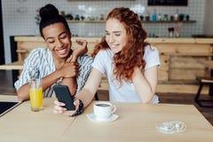 Многонациональные девушки используя smartphone Стоковое фото RF