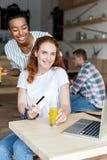 Многонациональные девушки с соком и кредитной карточкой Стоковое Фото