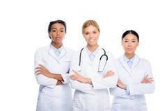 многонациональные женские доктора с стетоскопом и пересеченными оружиями, Стоковая Фотография