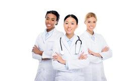 многонациональные женские доктора с стетоскопом и пересеченными оружиями, Стоковое Изображение RF