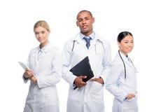 многонациональные женские и мужские доктора с стетоскопами, доской сзажимом для бумаги и цифровой таблеткой, Стоковое Изображение RF