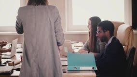Многонациональные занятые молодые работники офиса сотрудничают таблицей в живом coworking офисе, людях идут вокруг замедленного д акции видеоматериалы