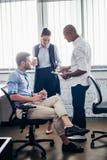 Многонациональные коллеги обсуждая в офисе Стоковое Изображение