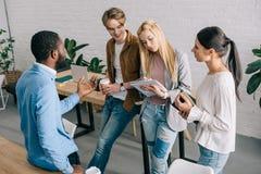 многонациональные предприниматели с кофе и учебниками имея обсуждение в современном стоковое фото