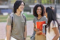 Многонациональная группа в составе молодые усмехаясь студенты стоя и говоря стоковое фото