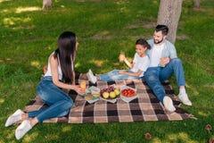 Многонациональная семья есть и выпивая пока отдыхающ на шотландке на пикнике Стоковые Изображения