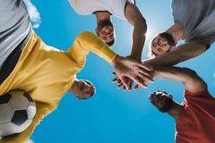 Многонациональная футбольная команда держа руки совместно перед игрой Стоковые Изображения