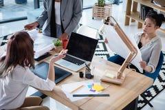 Многонациональные архитекторы работая на офисе с цифровыми приборами и светокопиями Стоковые Фото