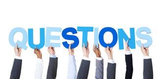Многонациональные бизнесмены держа вопросы о слова Стоковые Фотографии RF