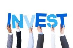 Многонациональные бизнесмены держа слово инвестируют Стоковые Изображения