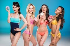 Многонациональные девушки в купальниках держа сладостные донуты Стоковые Фотографии RF