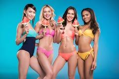 Многонациональные девушки в купальниках представляя с арбузом соединяют Стоковые Фотографии RF