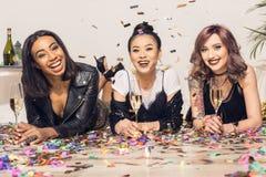 Многонациональные девушки лежа на поле с стеклами шампанского и смотря камеру Стоковое Изображение