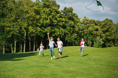 Многонациональные дети играя совместно пока бегущ с змеем в парке Стоковые Фотографии RF