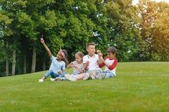 Многонациональные дети сидя на зеленом луге и дуя пузырях мыла в парке Стоковая Фотография